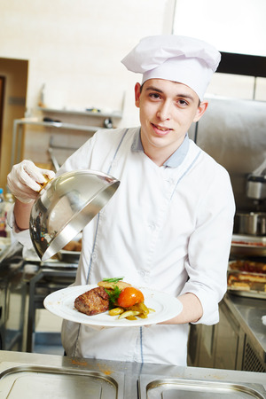 gourmet kitchen: young male cook chef with cloche and food on the plate in commercial kitchen Stock Photo