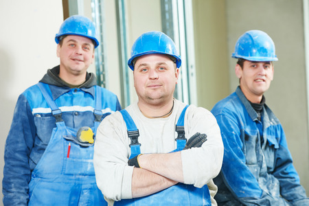 laborers: cheerful plasterboard workers team at a indoors wall insulation works