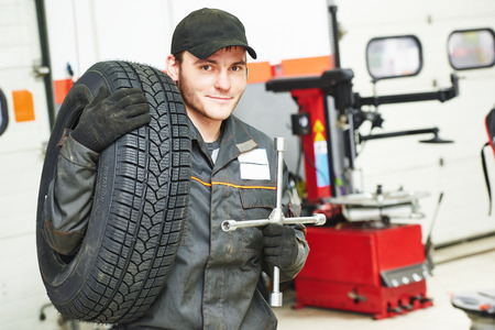 scheduled replacement: repairman mechanic portrait with tyre in car auto repair or maintenance shop service station with automobile wheel tire