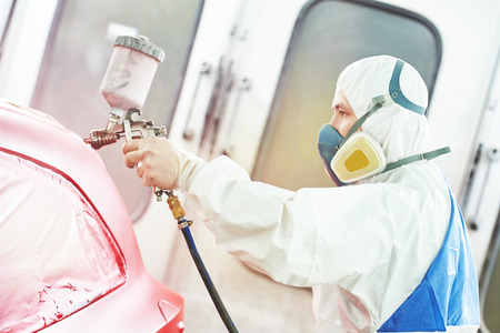 chamber: auto mechanic worker painting a red car in a paint chamber during repair work