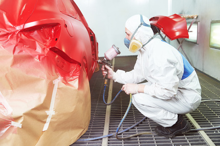 priming: auto repair worker painting a red car in a paint chamber during repair work