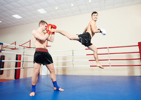 thai arts: muai thai sportsman fighting at training boxing ring