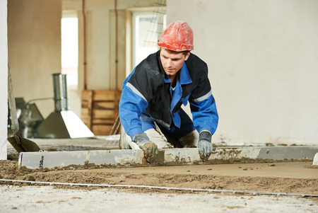 parget: Plasterer duing indoors concrete cement floor topping with float Stock Photo