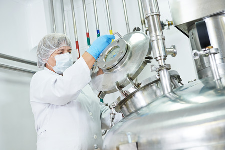 female worker operating pharmaceutical factory equipment mixing tank on production line in pharmacy industry manufacture factory