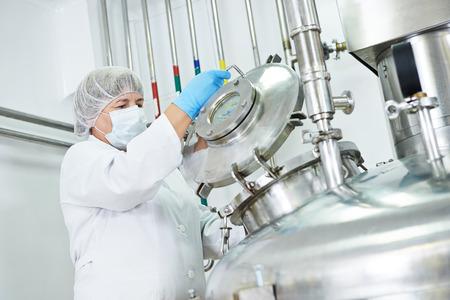 trabajador farmacéutica de funcionamiento del equipo de fábrica femenina tanque de mezcla en la línea de producción en la farmacia fábrica fabricación industria
