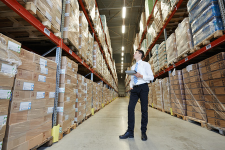 warehouse equipment: male manager man standing in big modern warehouse with tablet computer