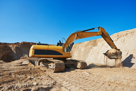 sand quarry: exavation machine excavator at earthmoving work in sand quarry Stock Photo