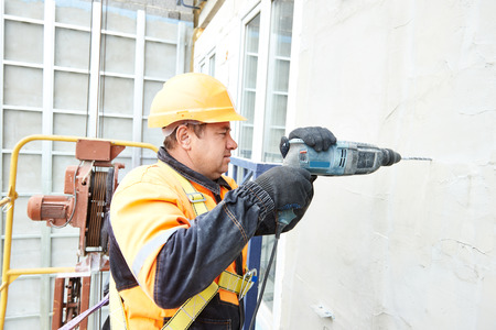 tile cladding: worker builder making construction for ventilation facade on a building with screwdriver drill