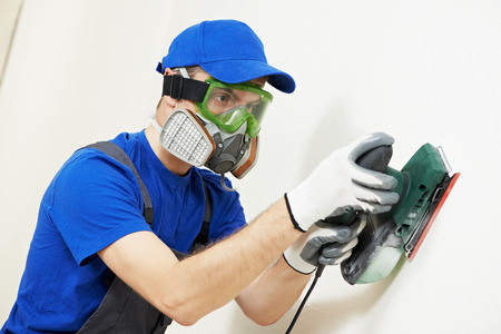Home improvement plasterer worker in protective mask and glasses working with sander for smoothing wall surface Stock Photo