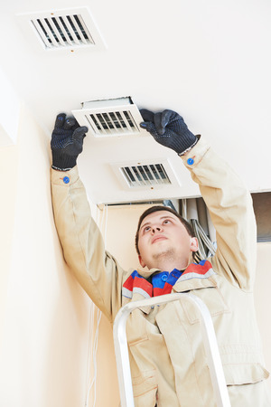 ceiling: industrial worker installing ventilation or air conditioning filter holder in ceiling