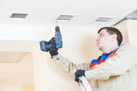 air filter: industrial worker installing ventilation or air conditioning filter holder in ceiling