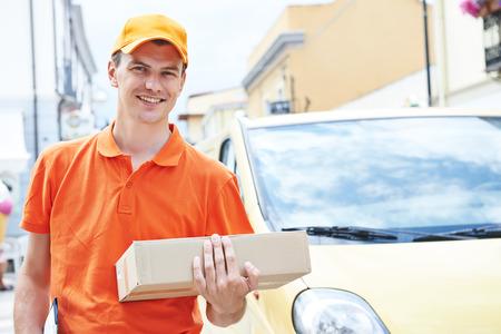 パッケージ配布する貨物バンの前に屋外郵便配達急使男の笑みを浮かべてください。 写真素材