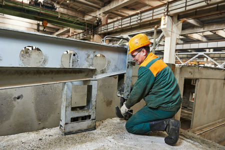 housebuilding: industrial worker at house-building plant factory workshop