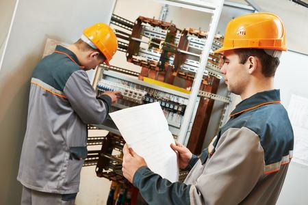 electricista: dos electricista ingeniero constructor trabaja con cableado eléctrico de la Caja de fusibles