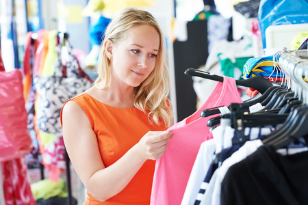 choosing clothes: woman choosing dress during shopping at garments apparel clothing shop Stock Photo