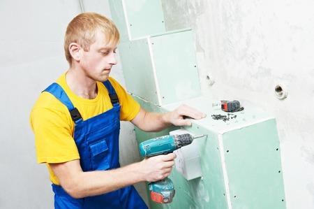 Carpenter joiner plasterer with screwdriver mounting gypsum plasterboard system at toilet