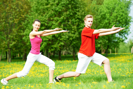loosen up: fitness man and woman doing physical stretching exercises during outdoors sport training