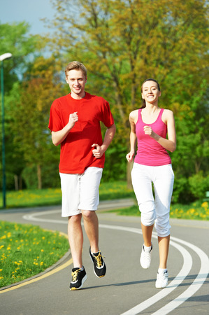 loosen up: Young fitness man and woman doing jogging run sport outdoors