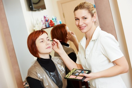 make up artist: Makeup technique. specialist works with mascara eyelashes of redheaded woman in beauty salon