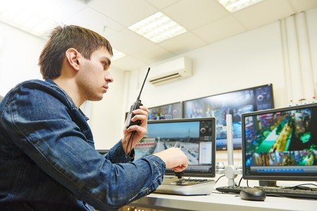 security guard watching video monitoring surveillance security system Stock Photo