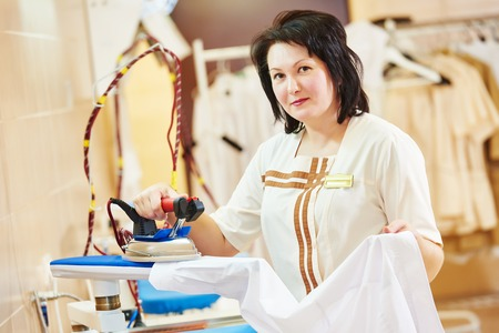 cleaning services. Woman with iron working at ironing shop Stockfoto