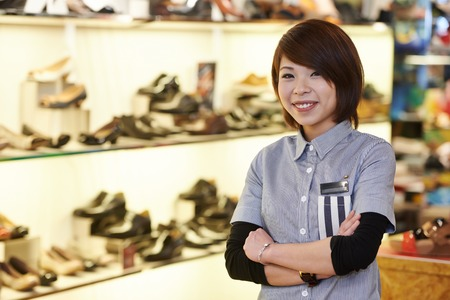 merchant: chinese young smiling female assistant seller in the shoe shop