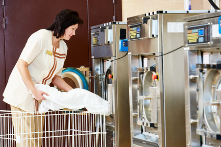 dry cleaner: cleaning services. Woman loading laundry washing machine with cloth