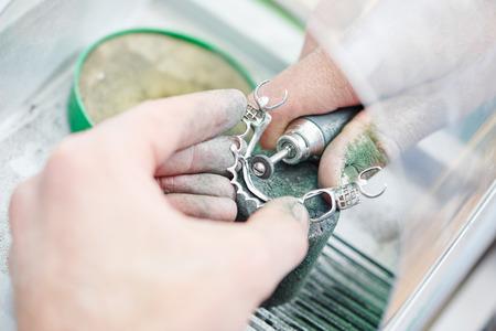 orthodontie: mains de prothèse dentaire orale traitement de technicien en métal avec l'outil de polissage pendant le travail sur les prothèses au laboratoire