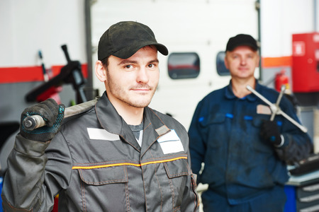 scheduled replacement: Two repairmans auto mechanic portrait in car auto repair or maintenance shop service station