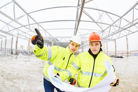 ingeniero: gerentes capataz ingenieros de construcci�n al aire libre en el interior en lugar de construcci�n con planos
