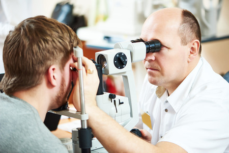 Male optometrist optician doctor examines eyesight of female patient in eye ophthalmological clinic Stock Photo