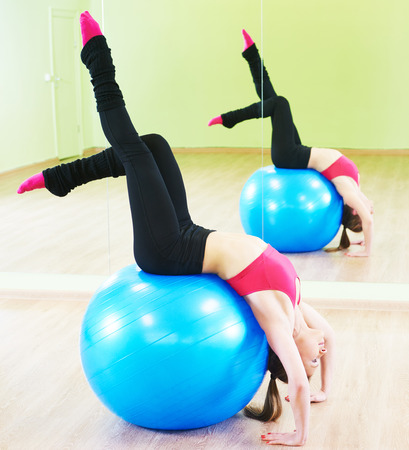 ball stretching: female instructor at stretching pilates exercises with finess ball in sport club Stock Photo