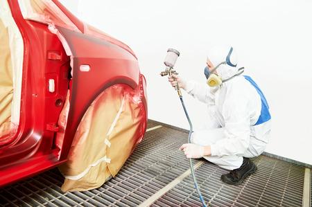 body paint: trabajador de la pintura de autom�viles. coche rojo en una c�mara de pintura durante los trabajos de reparaci�n Foto de archivo