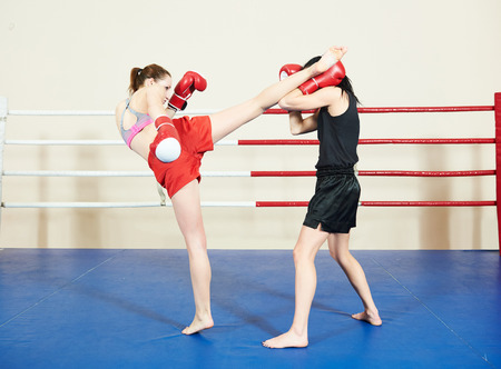 female kick: muai thai women fighting at training boxing ring