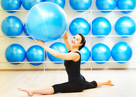 ball stretching: woman doing split with fitness ball during pilates stretching exercises in sport club
