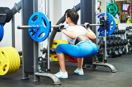 traction: fitness woman doing exercises for back muscles and buttocks with heavy weight