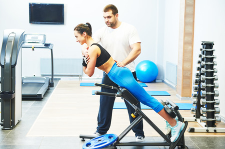 fitness and sport concept. personal coach trainer helps woman work out at a gym with heavy weight photo