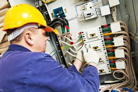alba�il: constructor electricista en el trabajo con el probador de medici�n de alto voltaje y la corriente de la l�nea de energ�a el�ctrica en fuseboard distribuci�n electical