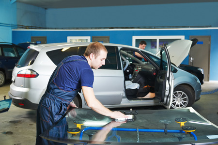 car manufacturing: Automobile glazier adding glue on windscreen or windshield of a car in auto service station garage before installation Stock Photo