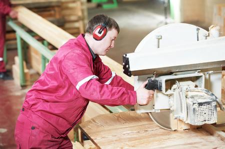 Closeup process of carpenter worker with circular saw machine at wood beam cross cutting during furniture manufacture photo