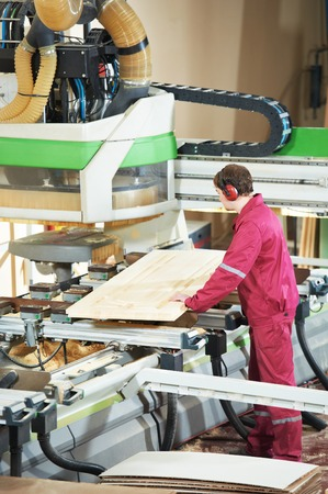 cabinet maker: industrial carpenter worker operating wood cutting machine during wooden door furniture manufacturing Stock Photo