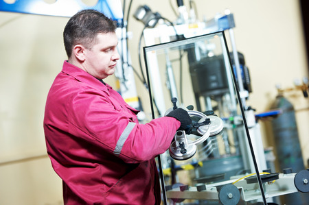 glazier: glazier worker with suction cup holding glass at double glazing window manufacture Stock Photo