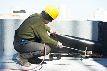 tar felt: Roofer preparing part of bitumen roofing felt roll for melting by gas heater torch flame