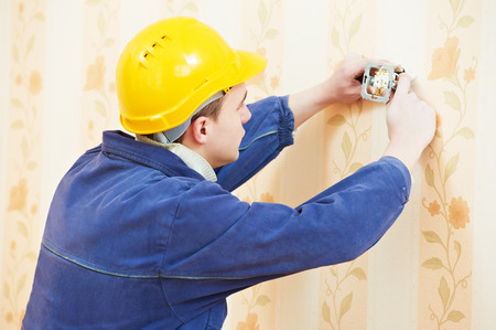 light worker: electrician worker at electric wall outlet or light switch socket installation work Stock Photo