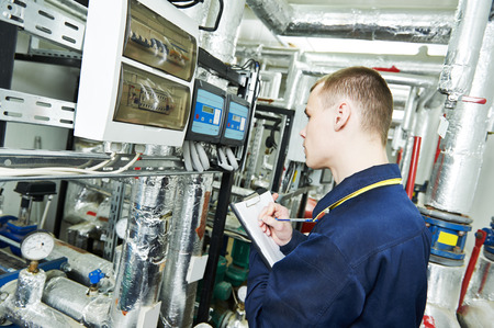 manometer: repairman engineer or inspector of fire engineering system or heating system with valve equipment in a boiler house
