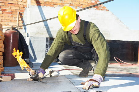 Roofer preparing part of bitumen roofing felt roll for melting by gas heater torch flame photo
