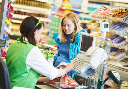 Customer buying food at supermarket and making check out with cashdesk worker in store Banque d'images