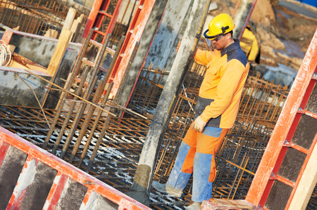 formwork: builder worker with boom pump pouring concrete on metal rods reinforcement of formwork