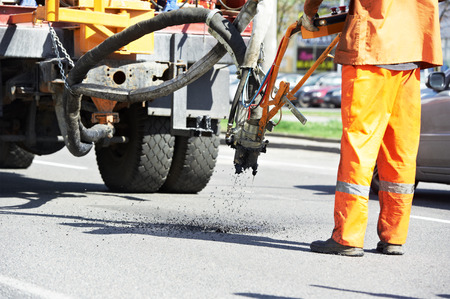 patching: Road worker at asphalt roadway street patching reaparing work Stock Photo