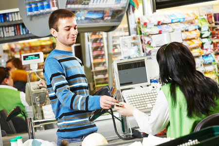 Customer buying food at supermarket and making check out with cashdesk worker in store 写真素材
